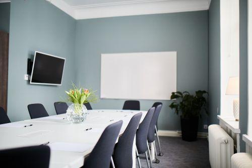 Lokal med styrelsesittning, whiteboard, smarttv och gröna växter