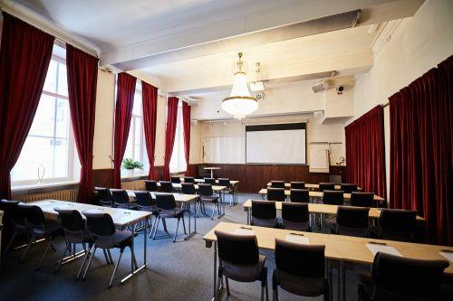 konferenslokal opalen med kristallkrona, skolsittning och röda gardiner