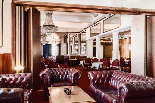 Röda rummet med chesterfield soffor, långbord med vita dukar, spelgar på väggarna och kristallkronor