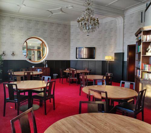 Lokal loungen med runda bord, storbildstv, bibliotekshyllor med logotype fönster och kristallkrona